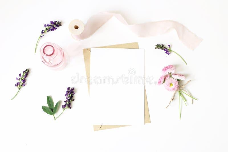 Feminine stationery, desktop mock-up scene. Vertical blank greeting card, craft paper envelope,silk ribbon, daisy and stock images