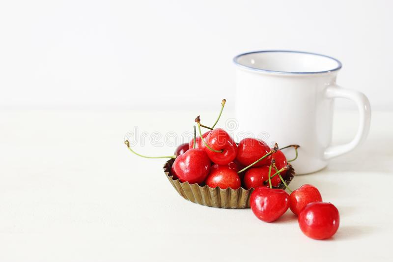 Feminine still life composition. White enamel coffee mug and sweet red cherry fruit in a little metal bowl on white stock photos