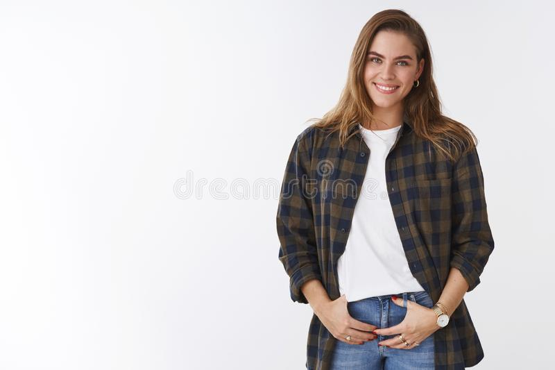 Feminine tender european girl giggling smiling broadly white teeth, wearing casual checked shirt holding hands pockets royalty free stock photo