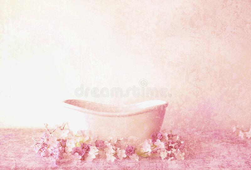 An antique Victorian bathtub with pink flowers and a pink textured background. A feminine victorian bathtub in pink, white and peach colors with an acrylic stock photography