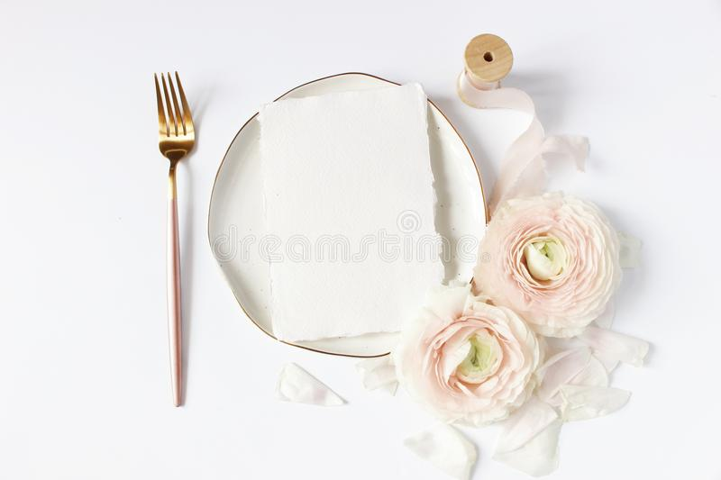 Feminine wedding, birthday desktop mock-up scene. Porcelain plate, blank craft paper card, silk ribbon, blush pink. Persian buttercup flowers and fork, white stock photography