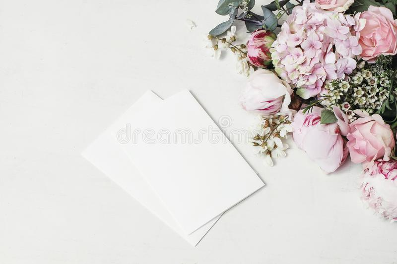 Feminine wedding, birthday mock-up scene. Decorative floral corner of peony, hydrangea, roses and locust flowers. Blank. Paper greeting cards on white wooden royalty free stock photography