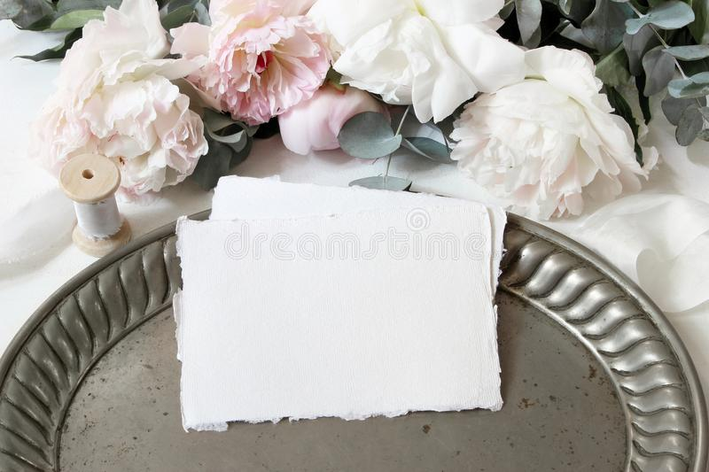 Feminine wedding or birthday table composition with floral bouquet. White and pink peonies flowers, eucalyptus, old royalty free stock photos