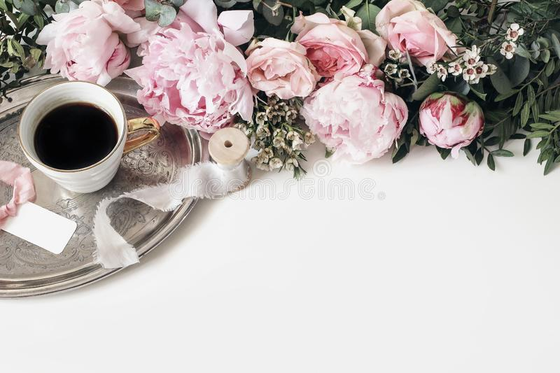 Feminine wedding or birthday table composition with floral garland. Pink peonies, roses, wax flowers, and green leaves royalty free stock images