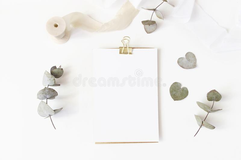 Feminine wedding desktop stationery mockup with blank greeting card, dry eucalyptus leaves, silk ribbon and golden. Binder clip on white table background, flat stock photography