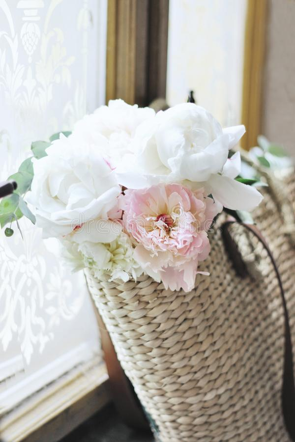 Feminine wedding still life composition. Straw French basket bag with pink peonies flowers and eucalyptus bouquet near. Old window. Styled stock photo for blog royalty free stock photos