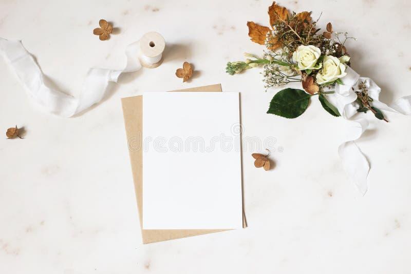 Feminine winter wedding, birthday stationery mock-up scene. Blank greeting card, envelope. Dry hydrangea, white roses. And gypsophila flowers bouquet. Marble royalty free stock images