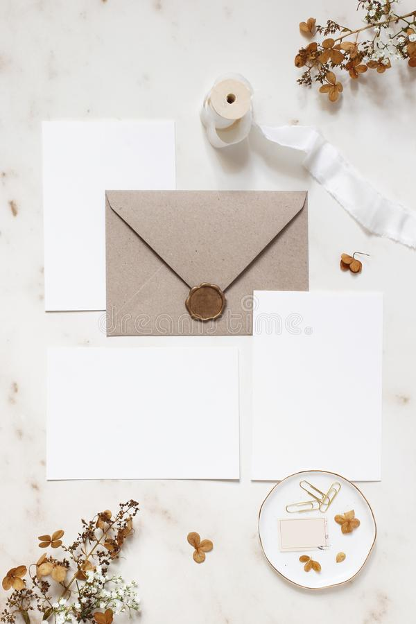 Feminine winter wedding, birthday stationery mock-ups scene. Blank greeting cards, envelope, wax seal, dry hydrangea and royalty free stock photos