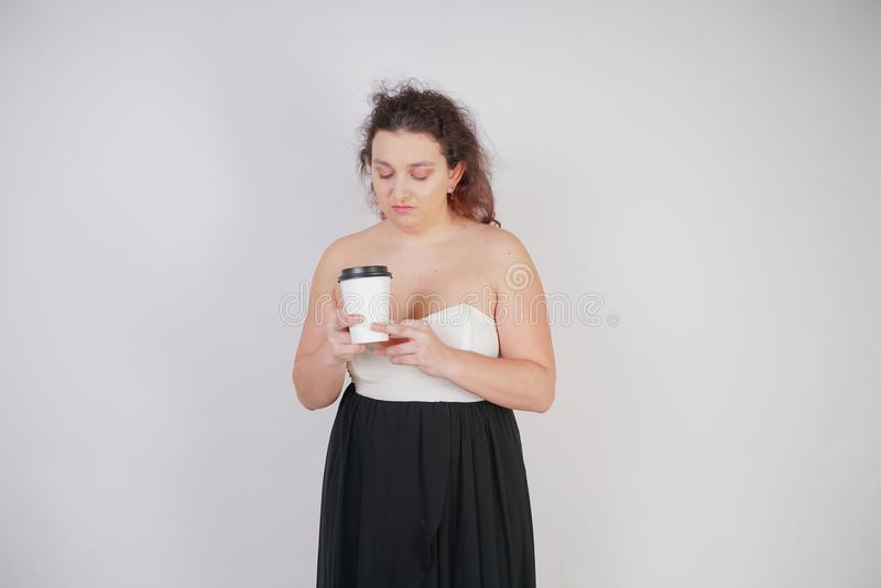 Feminine woman with plus size body in a fashionable dress holding a paper Cup of coffee and posing on a white background in the St stock images