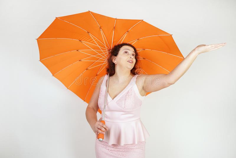 Feminine woman with plus size body in pink dress with orange big heart shaped umbrella posing on white background in Studio royalty free stock images