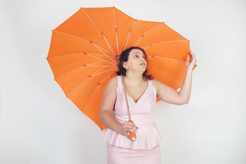 Feminine woman with plus size body in pink dress with orange big heart shaped umbrella posing on white background in Studio stock photography