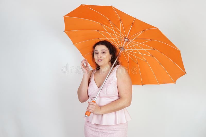 Feminine woman with plus size body in pink dress with orange big heart shaped umbrella posing on white background in Studio stock photo