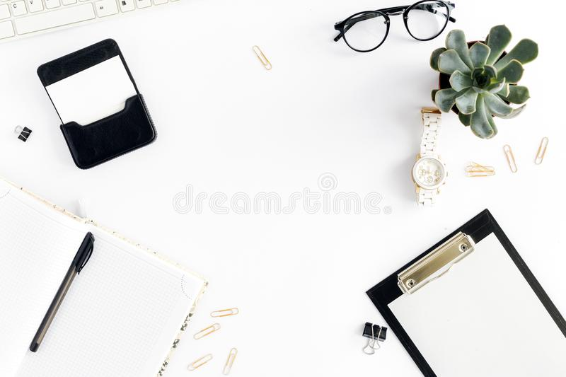Feminine workplace, clipboard, keyboard, notepad, glasses, succulents, watches, business card. Home office workspace. Feminine workplace with clipboard, keyboard stock photo