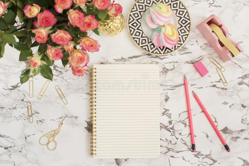 Feminine workplace concept. Freelance fashion comfortable femininity workspace in flat lay style with flowers, golden pineapple, n royalty free stock photography