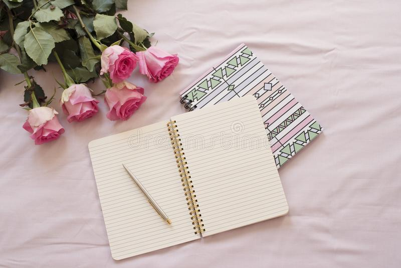 Feminine workplace concept. Freelance fashion comfortable femininity workspace in flat lay style with open notebook, pink rose flo stock photo