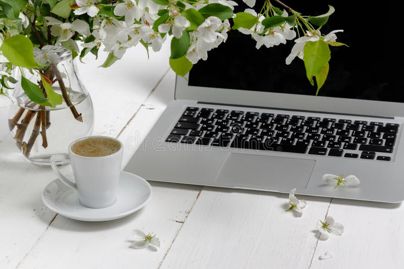 Feminine workplace concept. Freelance fashion comfortable femininity workspace  with laptop, coffee, flowers on white background royalty free stock photography