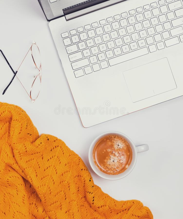 Computer, coffee and yellow sweater on the white background. Feminine workplace top view. Computer, coffee and yellow sweater on the white background royalty free stock photos