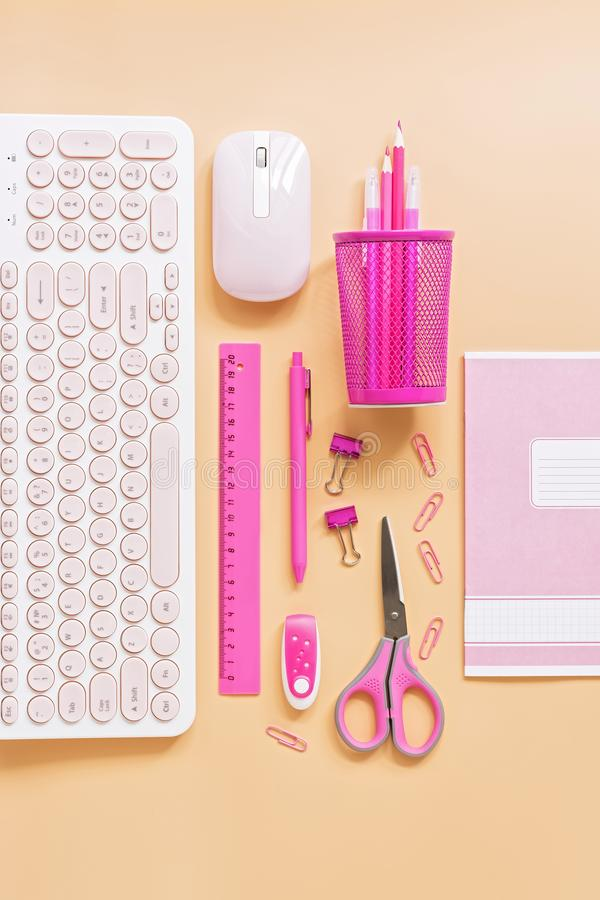 Feminine workspace with a computer and stationery to pink color on a pastel background. Flat lay office table desk frame.  stock photos