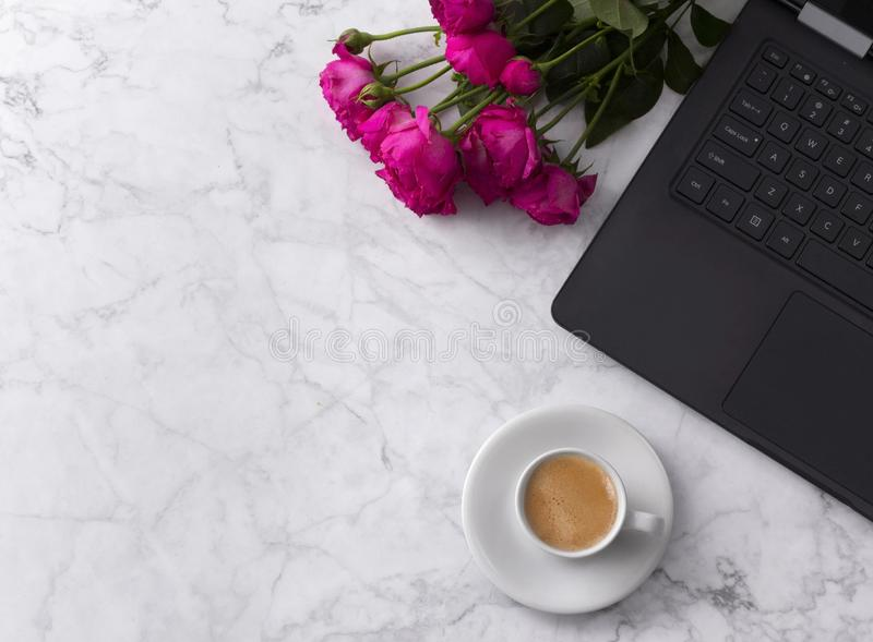 Feminine workspace with laptop computer, bouquet of roses and coffee on a marble table. Top view flat lay, copy space for your text or headline royalty free stock image