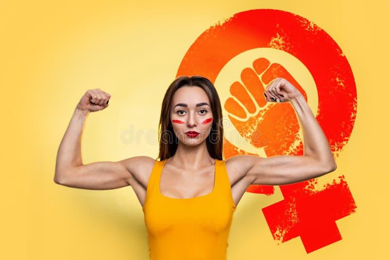 Feminismo e conceito de igualdade de direitos e independência para as mulheres Uma jovem caucasiana numa camiseta laranja mostra- imagens de stock