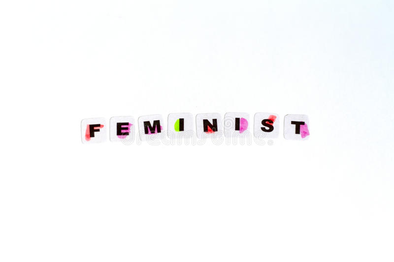 Feminist word written in black letters. On neutral background stock photos