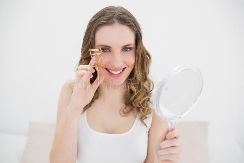 Femme à l'aide d'un bigoudi de cil image stock