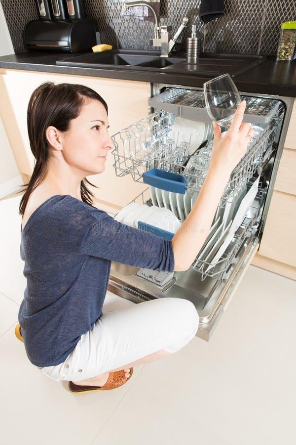 Femme à l'aide d'un lave-vaisselle dans une cuisine moderne photos libres de droits
