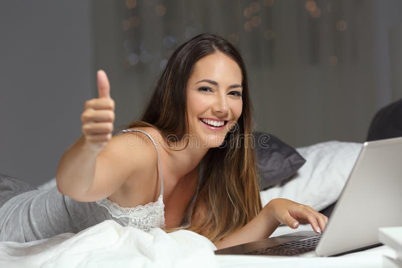 Femme à l'aide d'un ordinateur portable sur le lit avec des pouces  photo libre de droits