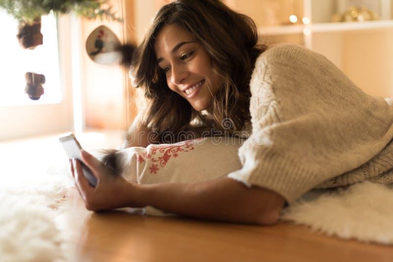 Femme à l'aide d'un smartphone à la maison photos stock