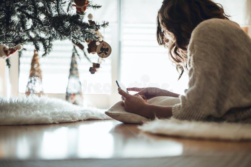 Femme à l'aide d'un smartphone à la maison photo libre de droits