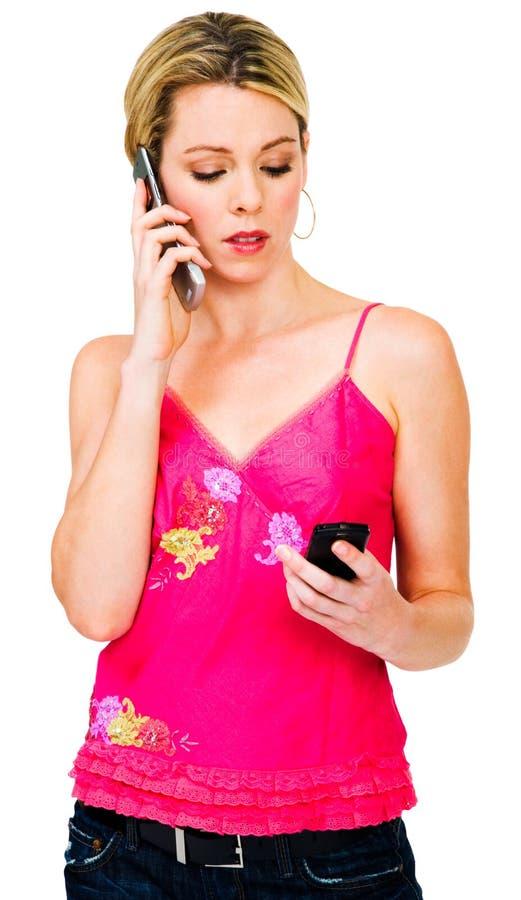 Femme à l'aide de deux téléphones portables image stock