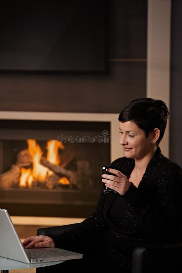 Femme à l'aide de l'ordinateur à la maison photos stock