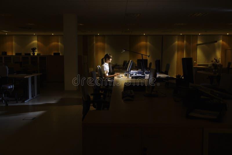 Femme à l'aide de l'ordinateur dans le bureau foncé image libre de droits