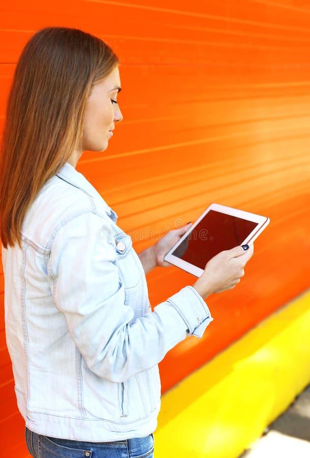 Femme à l'aide de l'ordinateur de PC de comprimé dans le profil au-dessus de l'orange photo libre de droits