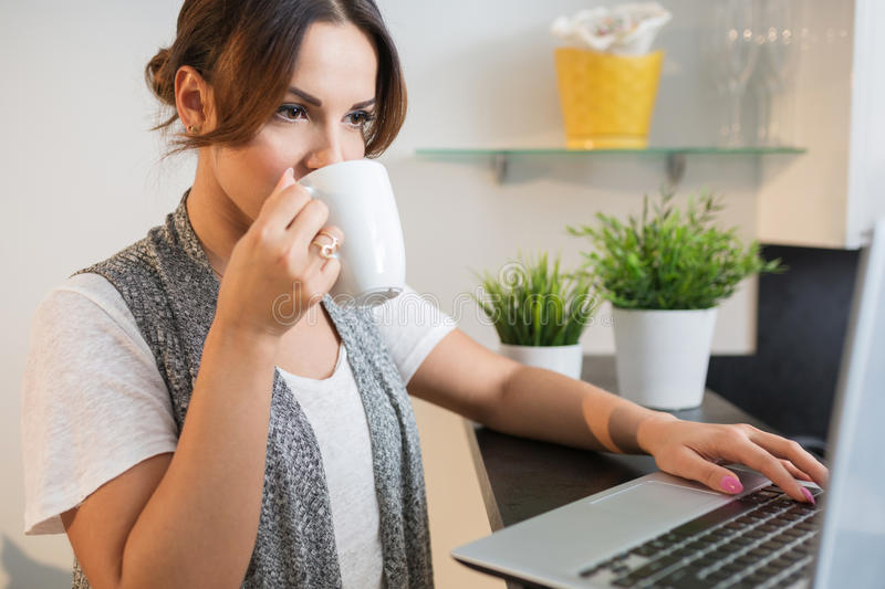 Femme à l'aide de l'ordinateur portable et buvant du thé photographie stock