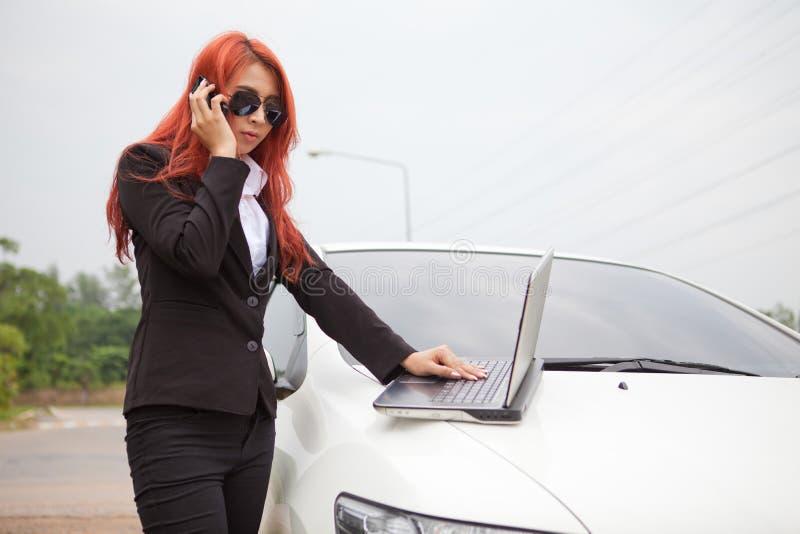 Femme à l'aide de l'ordinateur portable et du téléphone portable photo libre de droits