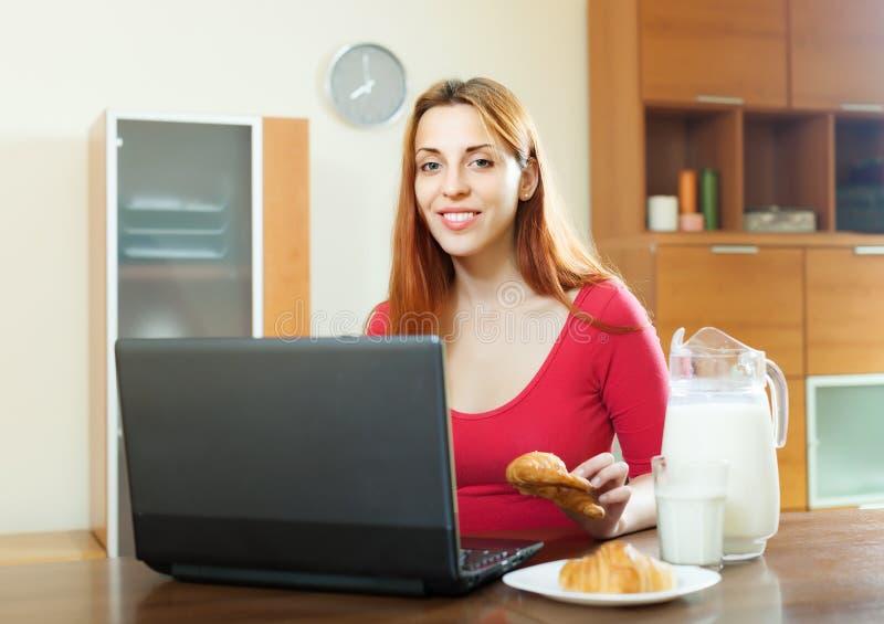 Femme à l'aide de l'ordinateur portable pendant le petit déjeuner photos libres de droits