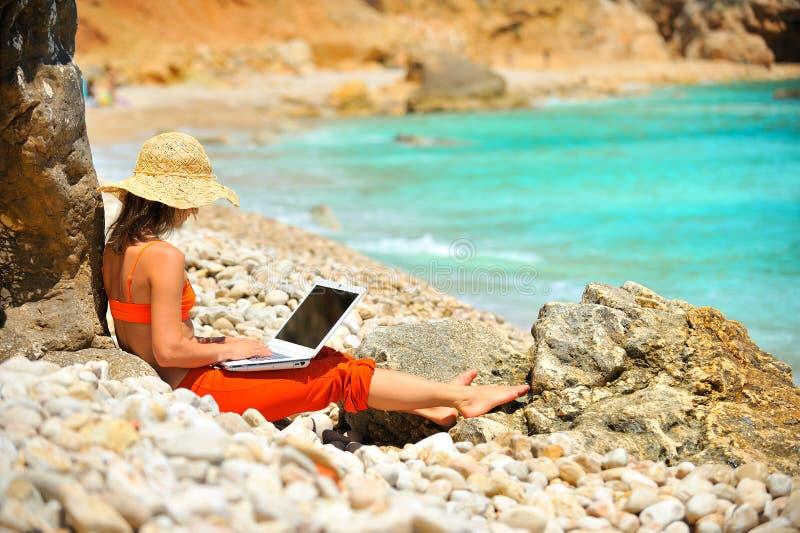Femme à l'aide de l'ordinateur portatif sur la plage images libres de droits