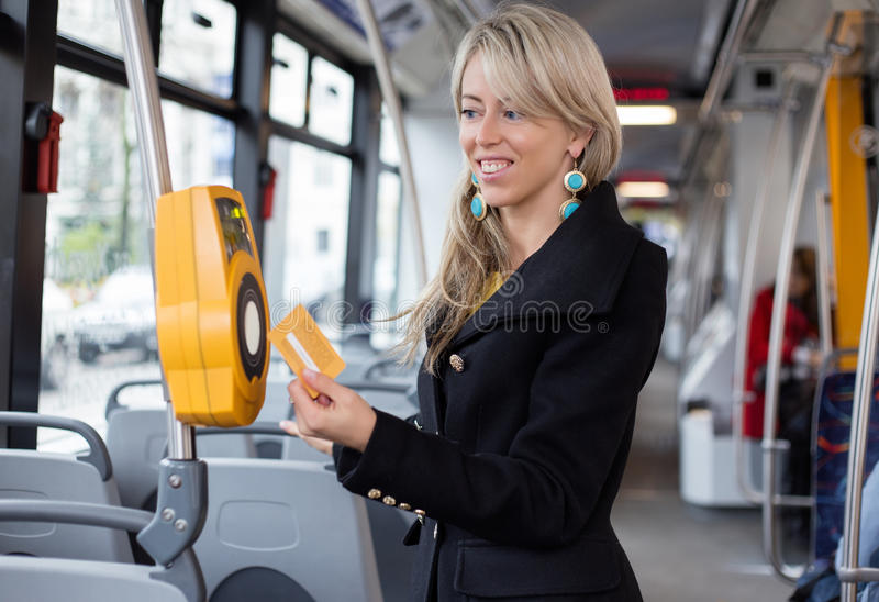 Femme à l'aide de la poinçonneuse de billet électronique dans le transport en commun image libre de droits