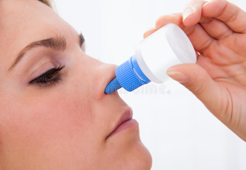 Femme à l'aide de la pulvérisation nasale photo stock