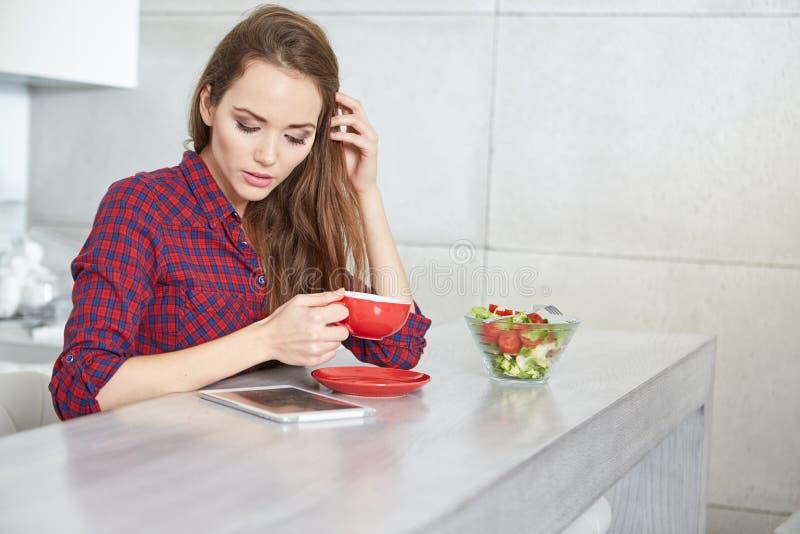 Femme à l'aide de la Tablette de Digital dans la cuisine photographie stock