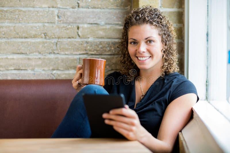 Femme à l'aide de la Tablette de Digital en café photo stock