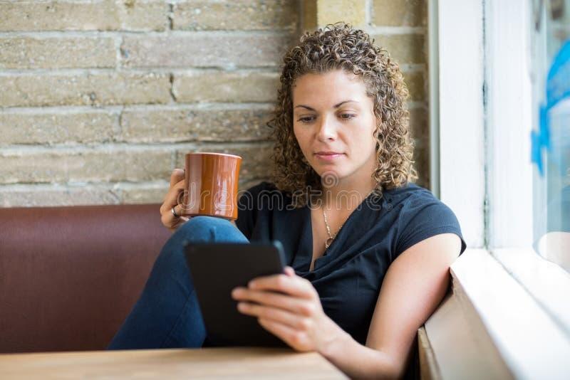 Femme à l'aide de la Tablette de Digital tout en ayant le café dedans photos libres de droits