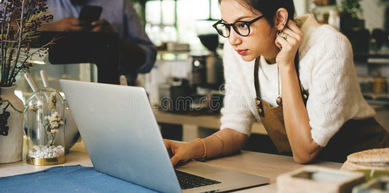 Femme à l'aide de l'ordinateur portable dans son bureau photo libre de droits