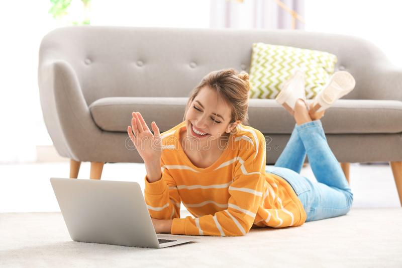 Femme à l'aide de l'ordinateur portable pour la causerie visuelle dans la chambre images libres de droits