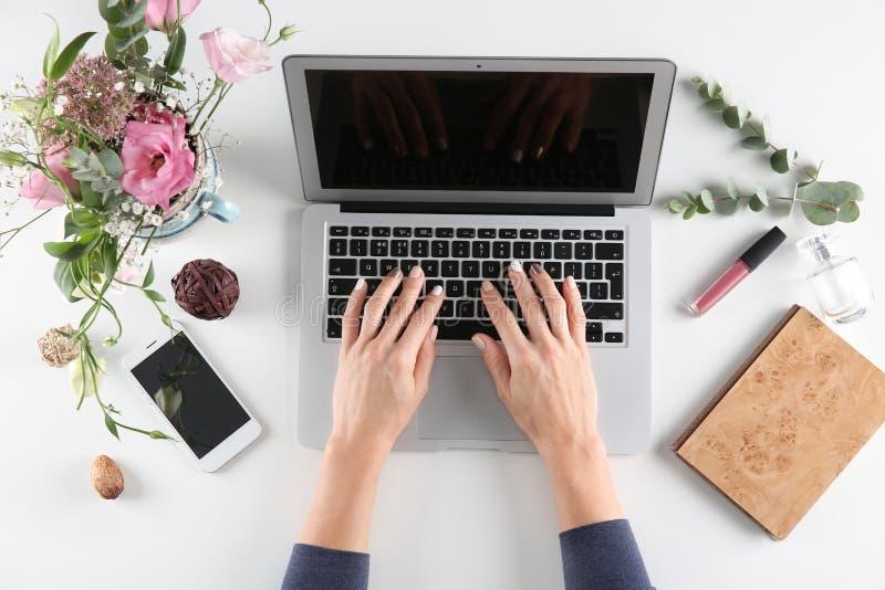 Femme à l'aide de l'ordinateur portable sur la table blanche photographie stock