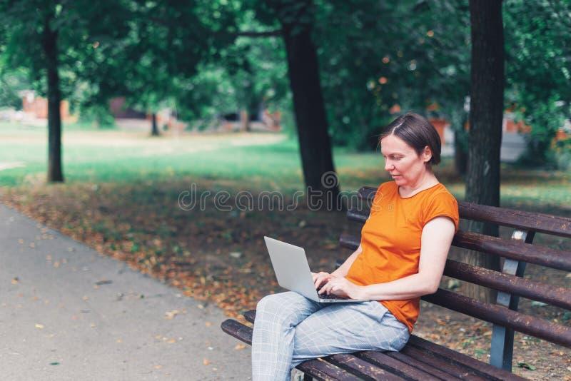 Femme à l'aide de l'ordinateur portable sur le banc de parc image libre de droits