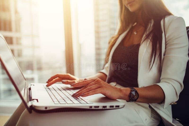 Femme à l'aide de l'ordinateur portable sur son recouvrement fonctionnant dans le bureau moderne images stock