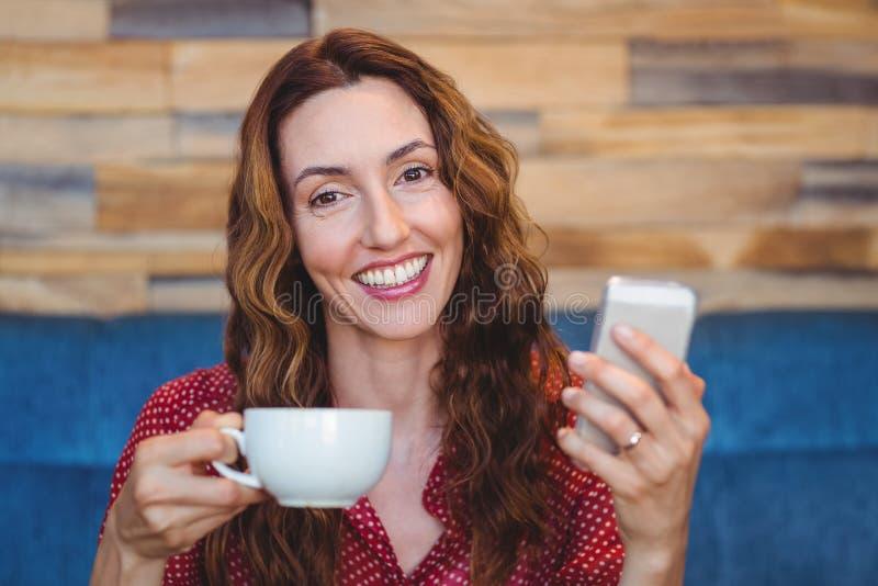 Download Femme à L'aide De Son Téléphone Portable Et Tenant La Tasse De Café Photo stock - Image du chaud, contact: 56486254
