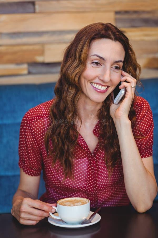 Download Femme à L'aide De Son Téléphone Portable Et Tenant La Tasse De Café Photo stock - Image du mobile, sourire: 56486258